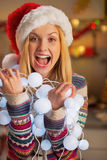 Teenager girl holding tangled christmas lights Royalty Free Stock Photos
