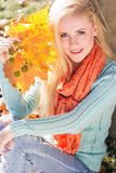 Teenager girl is holding yellow maple leaves Stock Images