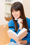 Teenager girl home - happy student with book Stock Photography