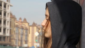 A teenager girl in a hoody with the hood on and loose multicolored hair against the graffiti, unfocused green traffic stock footage
