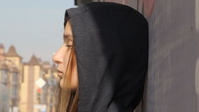 A teenager girl in a hoody with the hood on and loose multicolored hair against the graffiti, unfocused green traffic stock video