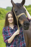 Teenager girl hugs the horse. Smiling girl taking care of the horse stock images