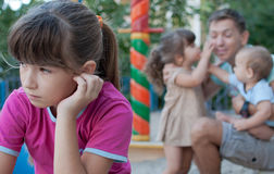 Teenager girl jealous of her younger sister and brother Royalty Free Stock Images