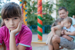 Teenager girl jealous of her younger sister and brother Stock Photo