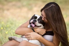 Teenager girl kissing her puppy Stock Image
