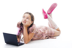Teenager girl with laptop thinking laying Stock Photos
