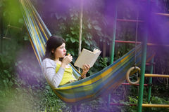 Teenager girl lay in hammock with book and kitten Royalty Free Stock Photography