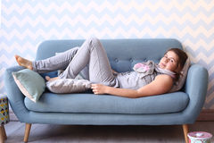Teenager girl lay on the sofa in pajama Stock Images