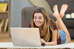 Teenager girl on line with a laptop at home Royalty Free Stock Images