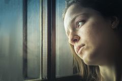 Portrait of a teenager girl thinking, sad, looking away next to royalty free stock image