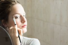 Teenager girl looking her self in a mirror applying eyeshadow wi stock images