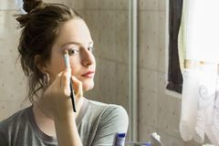 Teenager girl looking her self in a mirror applying eyeshadow wi royalty free stock images