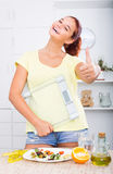 Teenager girl looking satisfied and holding scale on kitchen Stock Photo
