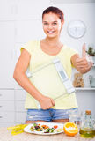 Teenager girl looking satisfied and holding scale on kitchen Royalty Free Stock Photo