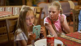 Teenager girl looking smartphone at dinning table. Young girl using mobile phone for watching video. Two girlfriends stock video