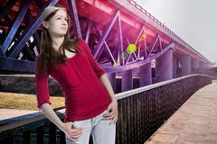 Teenager girl looking up, modern bridge background. Young pretty girl is looking upward and standing in pose on the path with handrail. New-design bridge Royalty Free Stock Photography