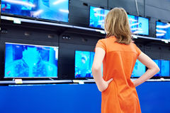 Teenager girl looks at LCD TVs in shop Royalty Free Stock Photo