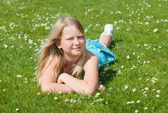 Teenager girl lying on grass. Blond teenager girl lying on the grass in a bright sunny day Royalty Free Stock Photo