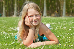 Teenager girl lying on grass. Blond teenager girl lying on the grass in a bright sunny day Royalty Free Stock Images