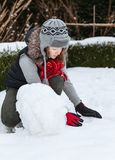 Teenager girl making snowman. In snowy back yard of her house Royalty Free Stock Photo