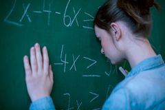 Teenager girl in math class overwhelmed by the math formula. Pressure, Education, Success concept. Student with head against blackboard Royalty Free Stock Photos