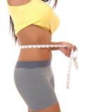 Teenager girl measuring tummy. Royalty Free Stock Photo