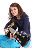Teenager girl musician playing acoustic guitar. Happy smile from pretty teenager girl musician sitting on floor playing music on acoustic guitar. She is wearing Stock Photos