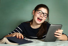 Teenager girl in myopia glasses play online game royalty free stock photography