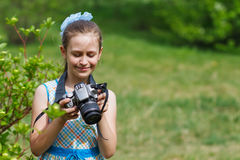 Teenager girl photographer at green forest. Small girl taking pictures in green field Royalty Free Stock Photos