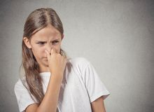 Teenager girl pinches nose, something stinks. Closeup portrait teenager girl with disgust on face pinches nose, something stinks, very bad smell, situation royalty free stock photos