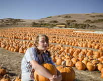 Teenager girl in plaid shirt choosing pumpkins Royalty Free Stock Images