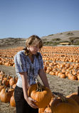 Teenager girl in plaid shirt choosing pumpkins Royalty Free Stock Photos