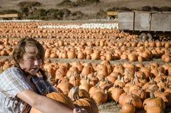 Teenager girl in plaid shirt choosing pumpkins Stock Image