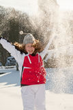 Teenager girl playing with snow in park. Happy teenager girl in a winter park throwing snow up - motion blur on girl's face Stock Photo
