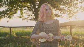 Teenager girl plays on ukulele, hipster with colored dyed hair resting sitting on grass with hawaii guitar