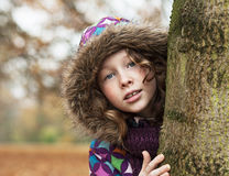Teenager girl poking around a tree. Teenager girl in colorful jacket poking around a tree trunk in an autumn park Royalty Free Stock Images
