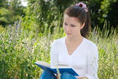 Teenager girl reading book. Sitting on the grass Stock Photos