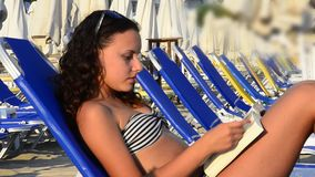 Teenager girl reading a book on a beach while sunb stock video footage