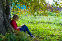 Teenager girl reading a book in forest. Teenager girl in red jacket sitting in forest and reading a bookr Royalty Free Stock Images