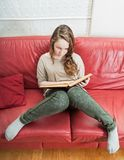 Teenager girl reading book. High angle view on teenager girl sitting on red leather sofa and reading book Stock Photos