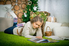 Teenager girl  reading a book. Vintage portrait of cute school girl reading a book in cold day. Girl in sweater lying on her stomach reading a book at home in Stock Photography