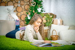 Teenager girl  reading a book. Vintage portrait of cute school girl reading a book in cold day. Girl in sweater lying on her stomach reading a book at home in Stock Photos