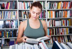 Teenager girl reading books in a bookstore stock photo