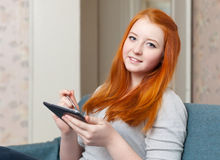 Teenager girl reads tablet computer at home Stock Photos