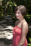 Teenager girl with red dress. At the park with green out of focus background Royalty Free Stock Photos