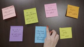 Teenager girl with red nails sticking two post it notes that contains motivational quotes next to others on a dark wooden desk -. Young teenager girl with red stock footage