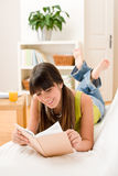 Teenager girl relax home - read book. Lying down on sofa Stock Image