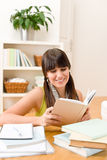 Teenager girl relax home - read book. Sitting down at table Royalty Free Stock Photos