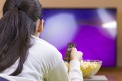 Teenager girl with remote control watching tv. Teenager girl with remote control laying down watching smart tv and eating popcorn Royalty Free Stock Image