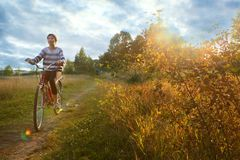 Teenager girl ride bicycle on the country field Stock Photography